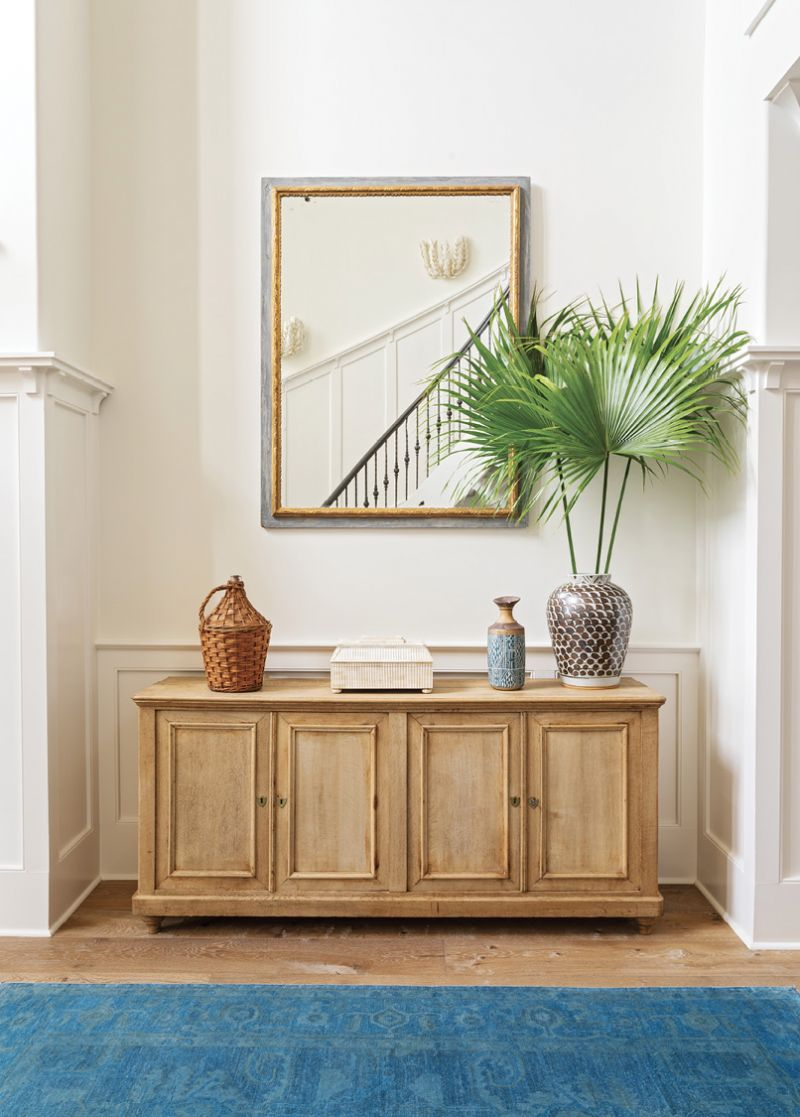 """AWASH IN WHITE: In the foyer, a sideboard from Acquisitions Interiors mimics the wainscotting design. For subtle contrast and depth, Allison painted the walls Benjamin Moore's """"Swiss Coffee"""" and the trim """"Simply White."""" A mirror from Alexandra AD reflects the grand staircase."""