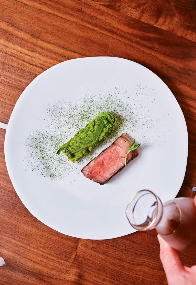 Worth the wait: Dry-aged beef is prepared on a Japanese Konro grill, which produces no sizzle or smoke while it gently sears and cooks the meat. A savoy cabbage leaf, stuffed with farro and kimchi, is served on the side.