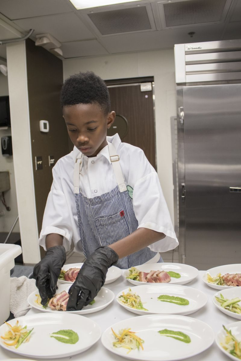 Jaylen Jones helps prepare the first course for guests.