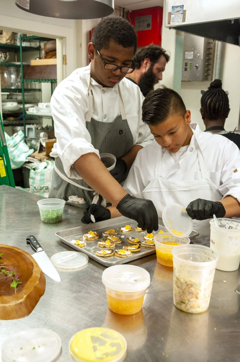 Former Little Chef and current Halls Signature Events intern Aiden LaFave helps Little Chef Abraham Aguilera put finishing touches on bruschetta.