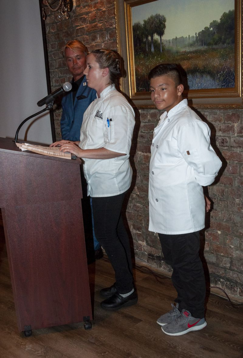 Louis Yuhasz stands by as Big Chef Robyn Guisto of Halls Signature Events and Little Chef Abraham Aguilera present their dish to dinner guests.
