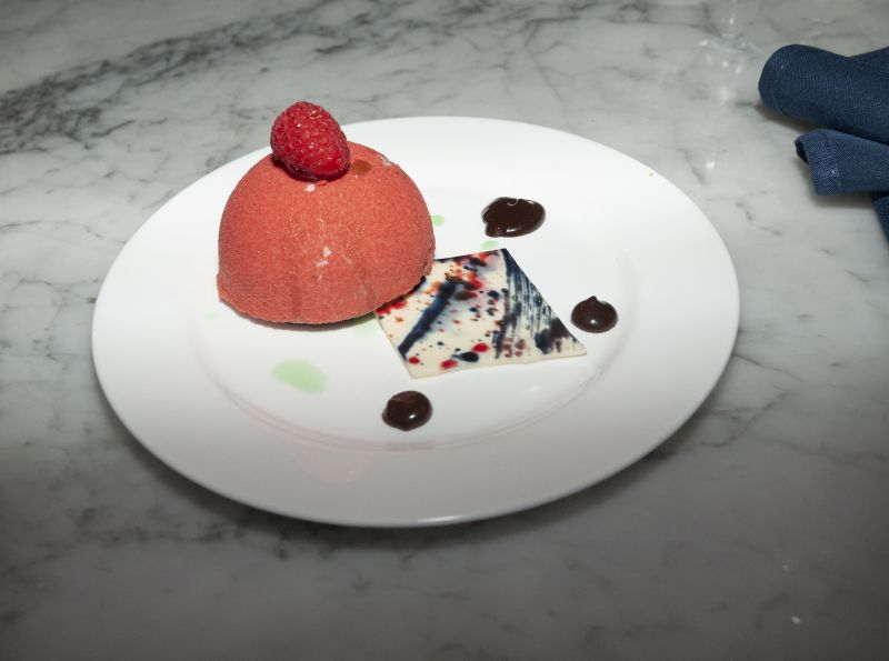 Raspberry mousse with a flourless chocolate sponge, raspberry filling, and chocolate fudge sauce, artfully crafted by Little Chef Isabella Hurd and Big Chef Richard Plaistowe of Halls Management Group.