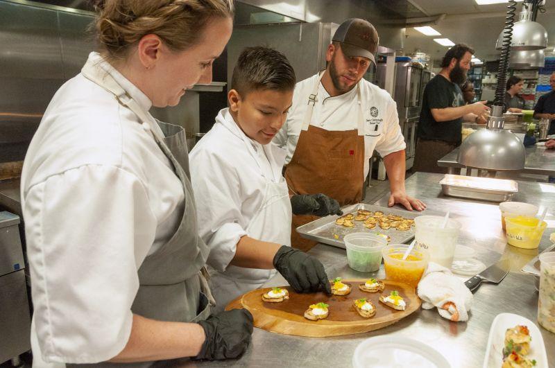 Big Chef Robyn Guisto of Halls Signature Events, Little Chef Abraham Aguilera, and Chef Samuel Cavanaugh of Glen Ridge Country Club plate bruschetta.
