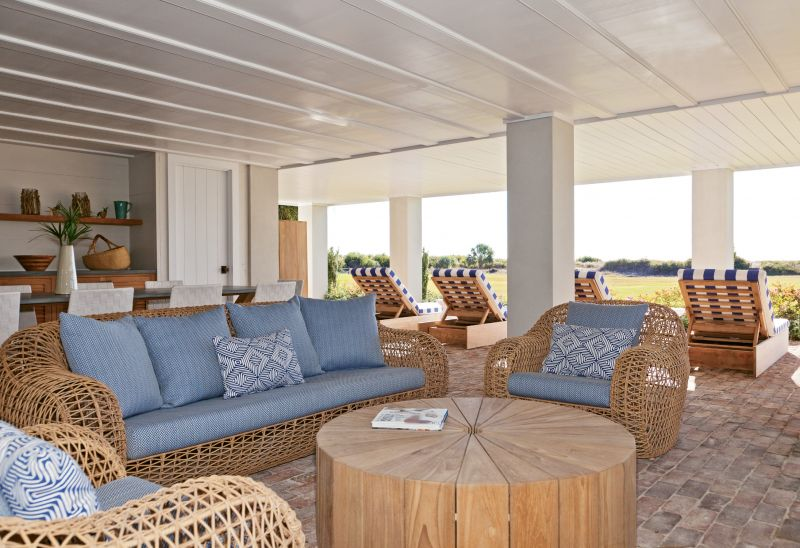Down Under: A breezy plein-air living room under the house includes an outdoor fireplace and bar, with room for entertaining or just lounging in the shade.