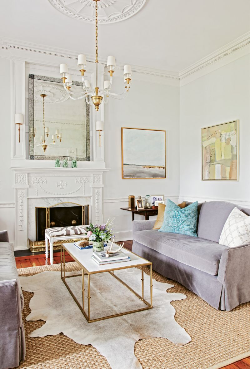 The home effortlessly blends original art, like the Slava Roubonov painting, Gathering, hanging above the sofa, with original architectural details such as the heart-pine floors, dentil mouldings, fireplace surround, and cypress wainscoting.