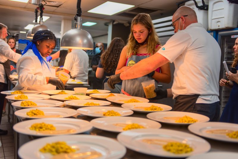 Little chefs Journee Myers and Claudia Hassell plate street corn.