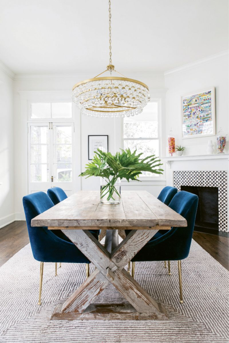 The luxe theme flows into the adjoining dining room thanks to velvet-covered chairs from Anthropologie and a Robert Abbey chandelier.