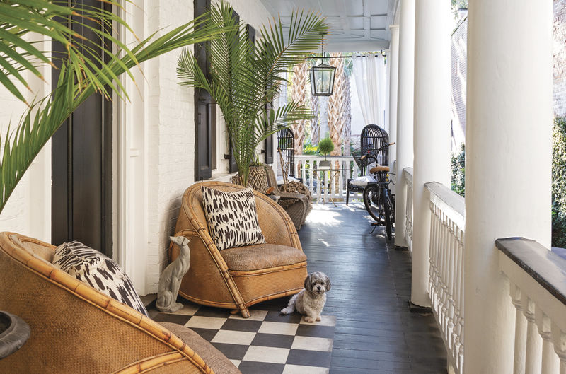 The furnishings on the piazza, such as the bold patterned pillows from Fritz Porter and the circa-1930s rattan chairs, hint at the blend of modern and vintage styles within.