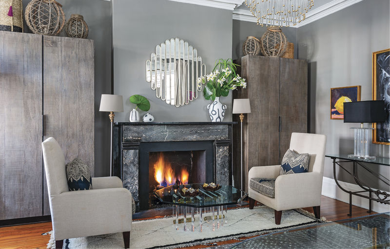 After dinner, the family turns their chairs to enjoy a fireside dessert by the glass and Lucite coffee table (also Patricia Allen Antiques). Restoration Hardware wall cabinets provide ample storage for this multipurpose room.