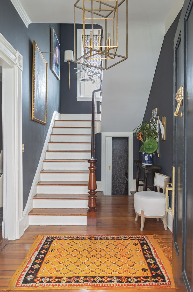 """High Contrast: The entry and stairwell are painted in Benjamin Moore's striking """"Wrought Iron."""" Offset by white trim and the wooden treads and handrail, the color adds personality to a utilitarian space and helps the gold accents (wall sconces and chandeliers from Circa Lighting) pop."""