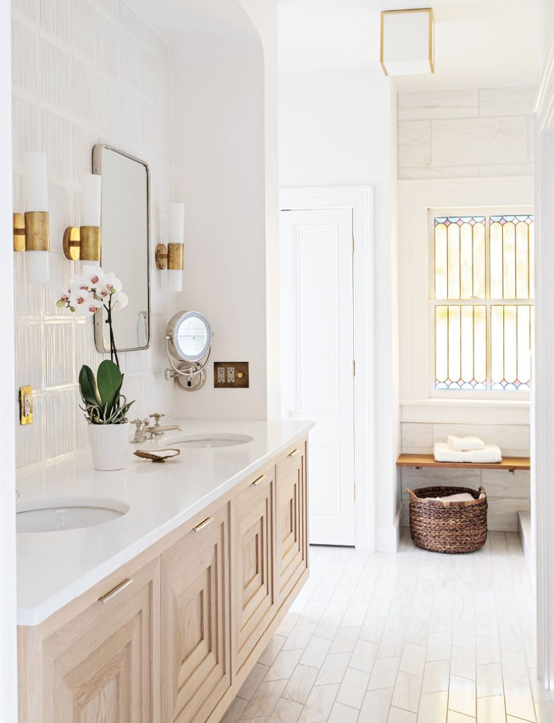 A hint of color from the original stained glass window is picked up in the brass wall sconces by Aerin. The white oak vanity with a stepped-front detail floats in the opposing arch from the adjoining bedroom.