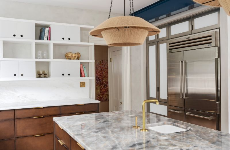 """Upper Crust: In place of traditional upper cabinets, Jill Howard designed a decorative floating wall storage unit with sliding doors to hide or reveal its contents. Similarly, a stainless steel """"appliance garage"""" built by Hostetler Custom Cabinetry secrets away clutter such as a toaster and microwave."""