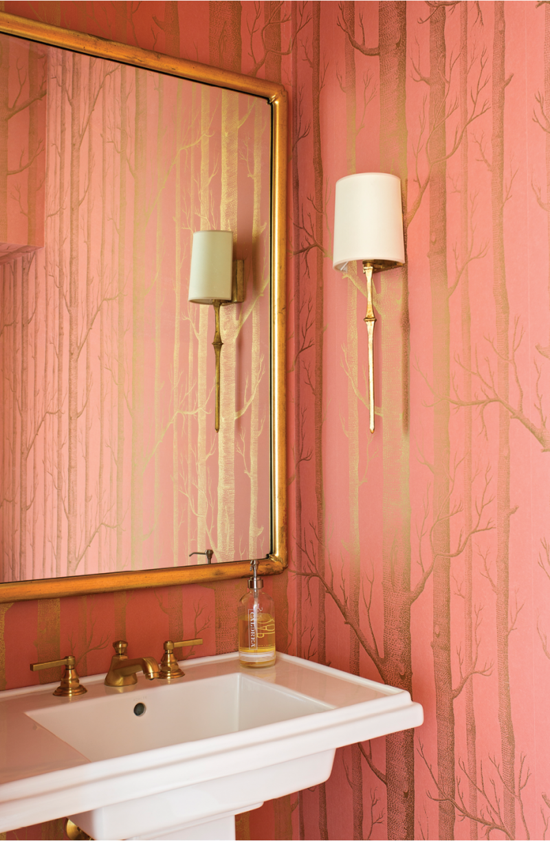 The powder room dazzles in radiant gold-flecked Cole & Son wallpaper, accented by a mirror found at John Pope Antiques and delicate sconces from Circa Lighting.