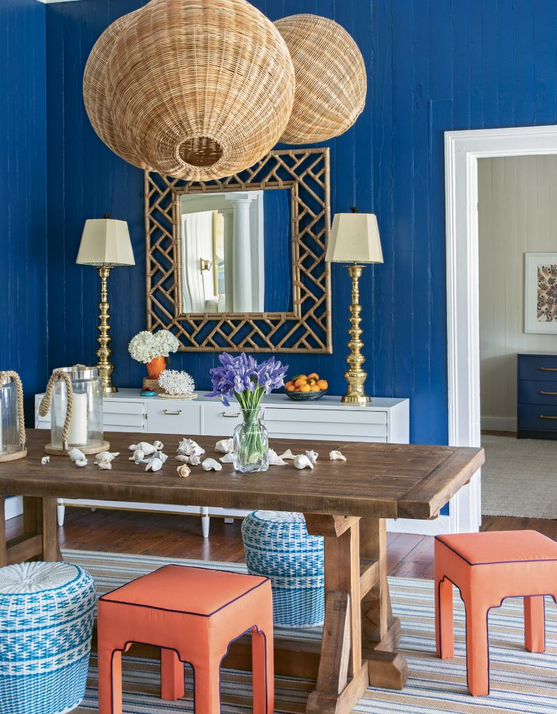 Woven Whimsy: A custom-designed cluster of wicker pendant lights from Serena and Lily dominates the reimagined entryway/dining room. A vintage cabinet from Indigo Market provides storage space as well as a showcase for two striking lamps from Chairish and mirror from Candelabra.