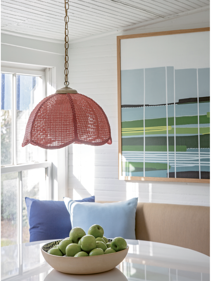 Color Play: A vintage red wicker pendant light in the breakfast nook is one of the homeowner's favorite finds. A painting by Isle of Palms-based artist Cindy DeAntonio presides over the scene.