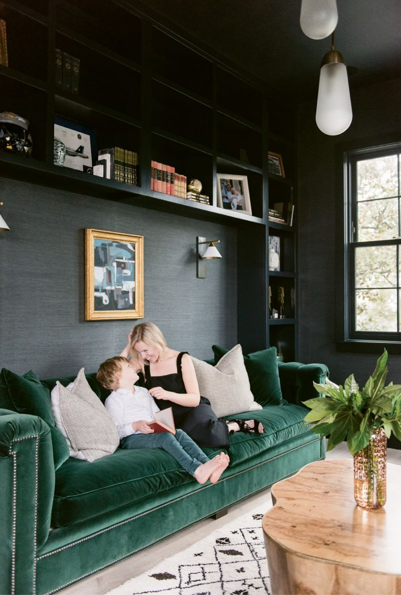 """Molly and Sawyer read in the library, where the Phillip Jeffries """"Manila Hemp"""" wallpaper in """"charcoal"""" and Hickory Chair sofa upholstered in emerald-green velvet by Ralph Lauren set a moody, masculine tone."""