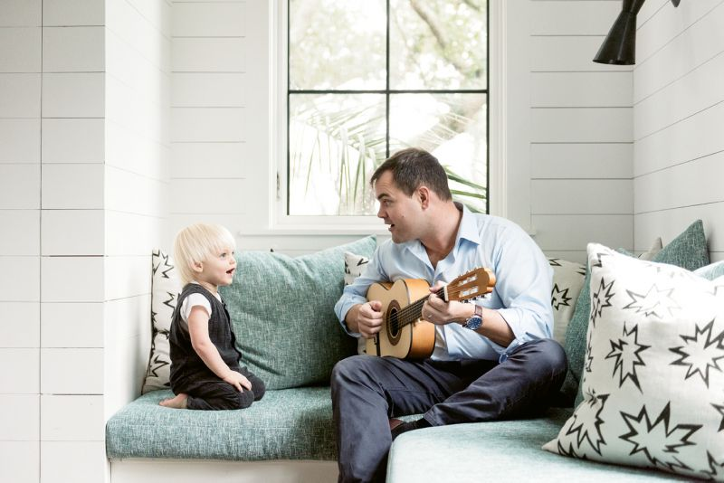 Ted serenades Fox in the nursery amongst pillows upholstered in playful comic book-inspired fabric.