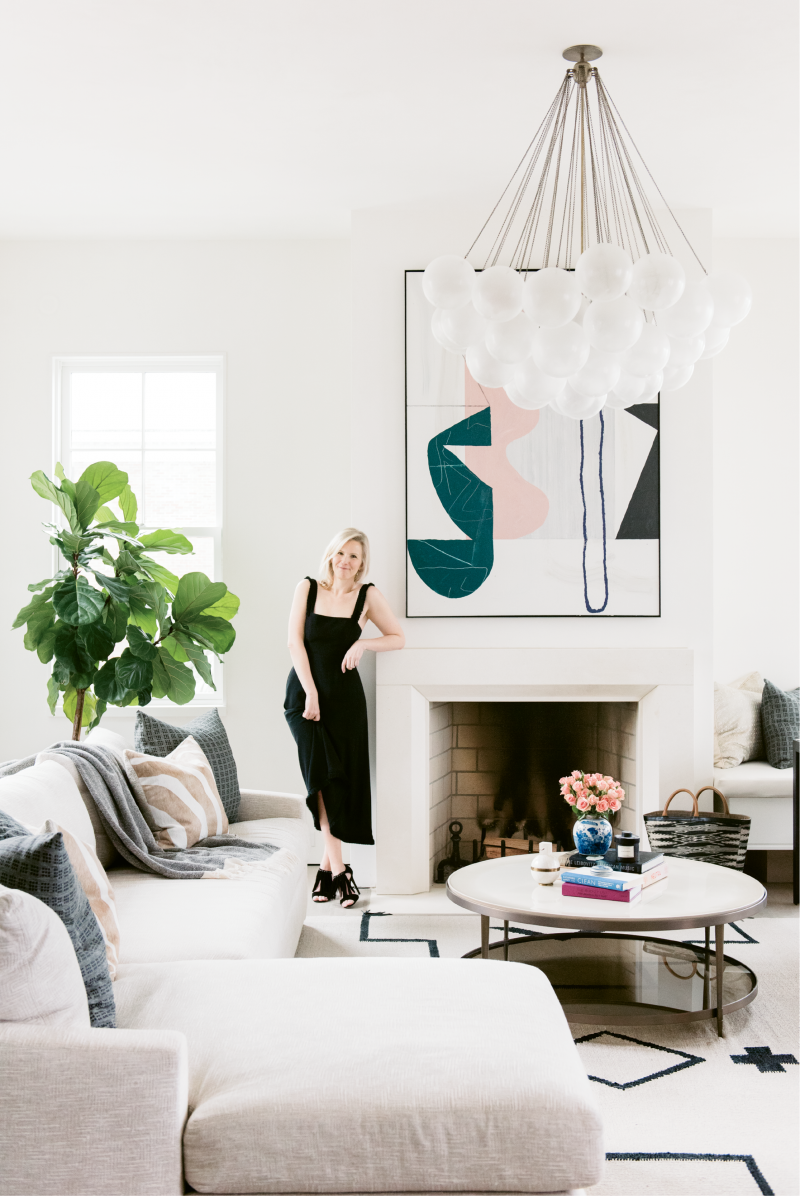 """Molly Fienning in the living room near an abstract painting by Brian Coleman; """"I fell in love with his work at the George Gallery downtown, so we commissioned him to create sister paintings that complement one another,"""" she says."""