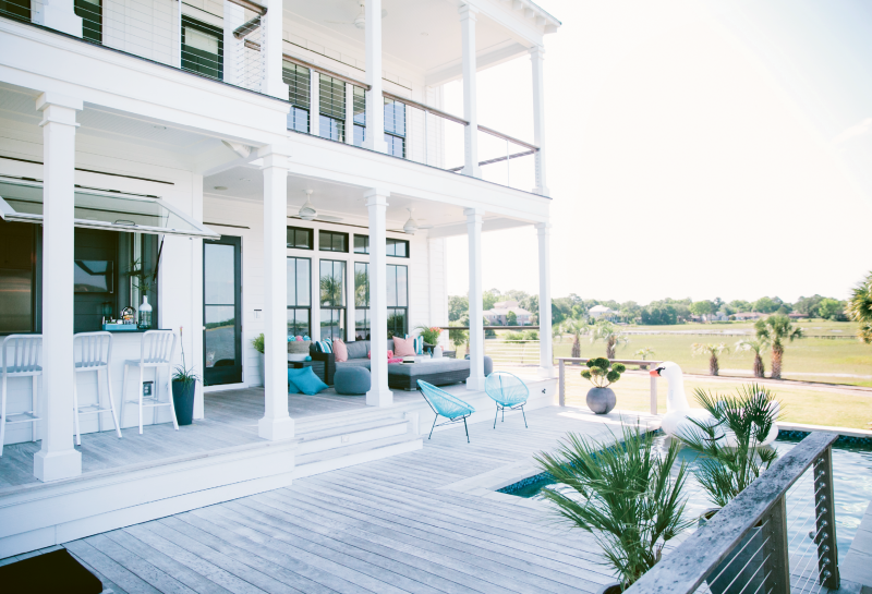 The patio is tiered so that pool activity won't obstruct the striking river views; the flip-open window on the indoor-outdoor bar allows for easy access to the kitchen.