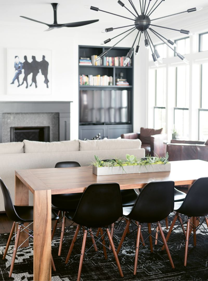 """She also layered in edgy accessories, such as the angular light fixture from Design Within Reach above the dining table and a graffiti-style painting above the living room mantel that reminds her of """"the dark side of corporate America."""""""