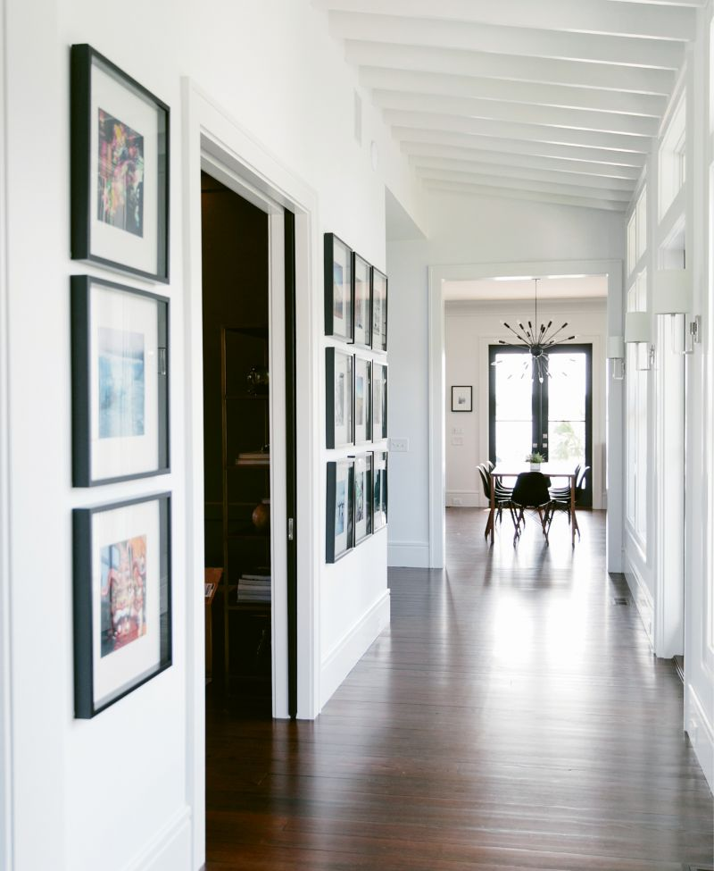 Melissa and Phil Clarke designed the entry hall's slanted, beadboard ceiling to mimic the look of an enclosed porch. Her office is through the pocket doors to the left; at the end of the hall, the open cooking, dining, and living space feels like a totally separate zone.