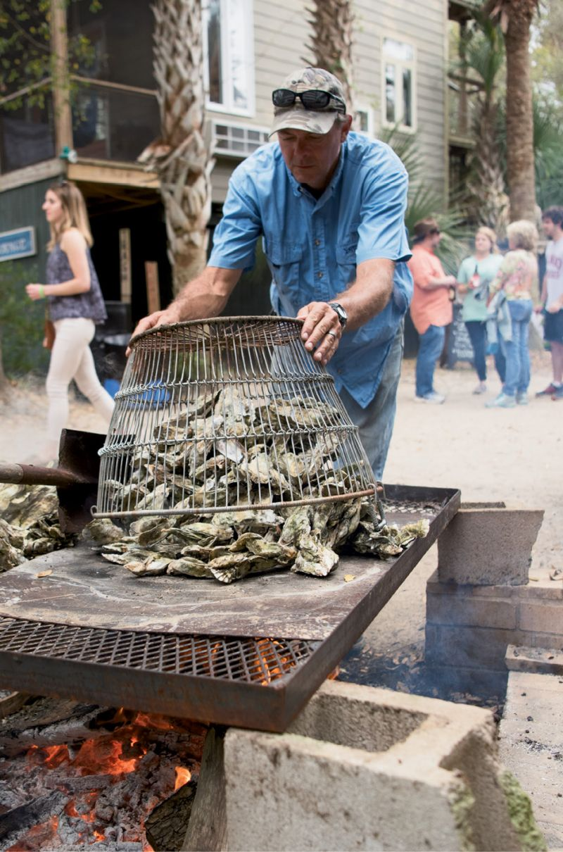 Robbie Cowart shoveled oysters onto  an open-fire grill for hungry guests.