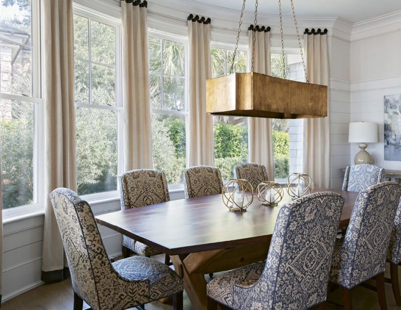 DINNER WITH A VIEW: The home's formal dining room embraces the outdoors, courtesy of a large wall of windows carefully curved to capture the view of a small olive grove. The custom black walnut dining table, handmade by John Grisanti of Redwood Lumber Company in New York State, curves to the exact contour of the outer wall. A Gabby chandelier and Bernhardt chairs bring a sense of grandeur to the room.