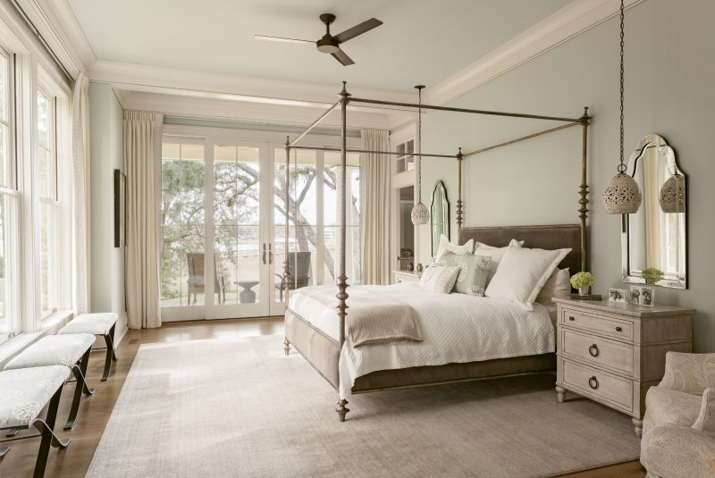 An upholstered four-poster bed from Southeastern Galleries welcomes views of the creek and the garden into the master bedroom. Pendant lights from Currey and Company replace traditional bedside table lamps, and large chests help reduce clutter in this calming space.