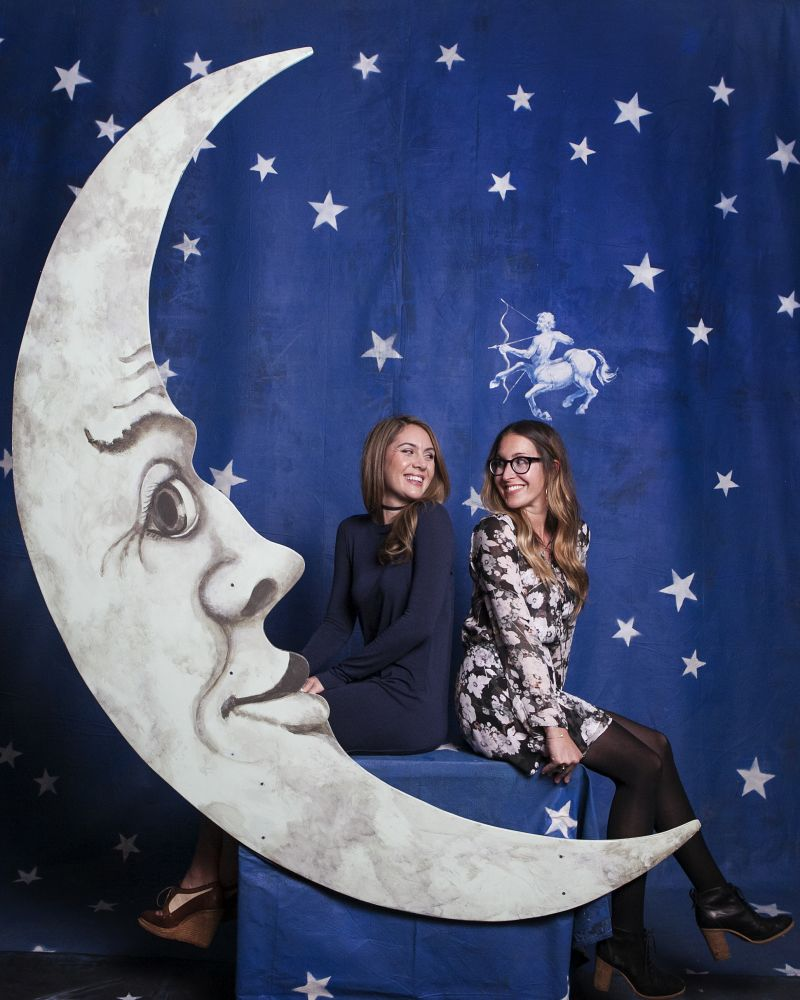 """Michelle Hurst and Lisa Roy pose in the signature """"Moon Booth."""""""