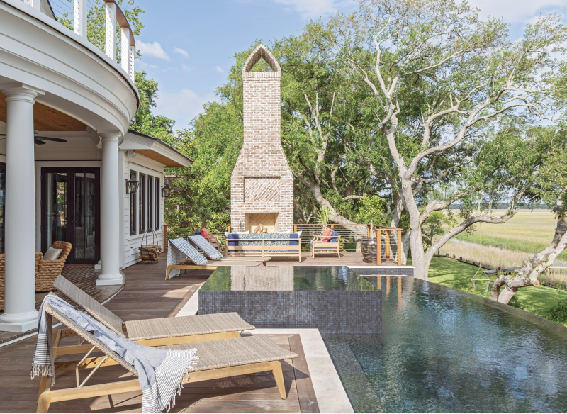 A traditional brick fireplace presides over the expansive pool deck. Its design, and other brickwork throughout the home, was inspired by Middleton Place, where Martha worked at as a teenager.