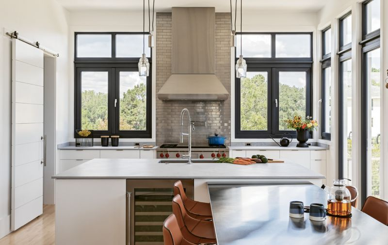Stainless steel dominates the kitchen for practical reasons (it's durable and easy to clean) and for visual effect—the ceiling-high backsplash with metal subway tile is a striking modern statement.