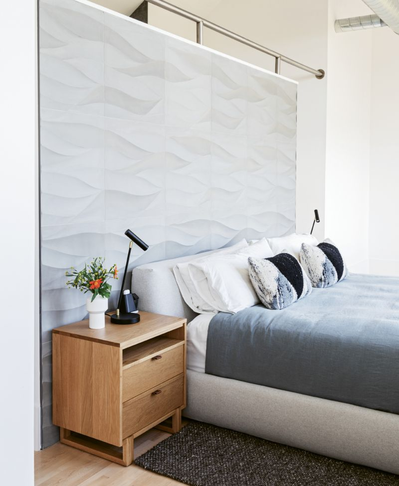 """CLEAN & RESTFUL: Simplicity reigns in the master bedroom, where a European platform bed and two oak nightstands are the only furnishings. Handmade Lithuanian bed linens and pillows, as well as a deep gray rug, add tonal interest, while two task lights provide just enough artificial light. """"We chose not to have many overhead light fixtures,"""" explains Steve, """"as there's so much natural light in the house."""""""