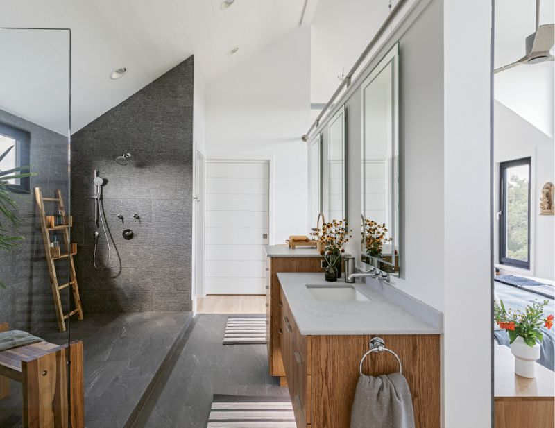 The unique open-plan master bathroom features a dramatic tiled shower and two floating vanities, supported by a freestanding wall that separates it from the bedroom. Touch-enabled LED lighting is built into the mirrors.
