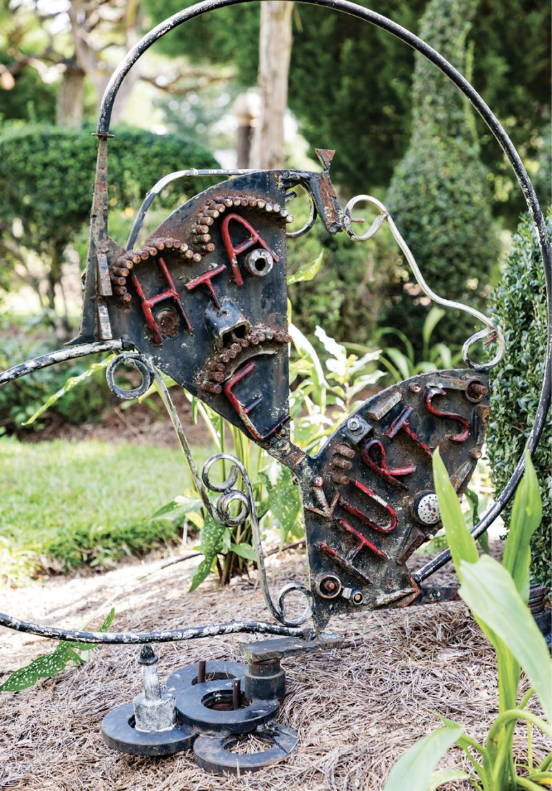 """WORDS OF WISDOM: Over the years, Fryar has added more fabricated sculptures as counterparts to shrubs and trees. He uses metal pieces, pottery, bottles, and other found objects. Sometimes he adds lettering, such as for the metal sign with """"Hate hurts"""" and an arrow pointing downward. The other side reads """"Love and Unity,"""" with an arrow pointing upward."""
