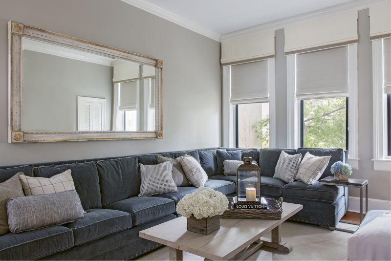 """Rick's only request for the décor? """"He said he wanted a really comfortable couch,"""" says Kristy. The custom sectional from Vanguard offers plenty of seating in the family room. Instead of elaborate window treatments that could easily overtake the decor, Peake chose light-hued, space-saving woven shades and had the window mullions painted in """"Kendall Charcoal"""" by Benjamin Moore for a modern look that highlights the woodwork while creating depth."""