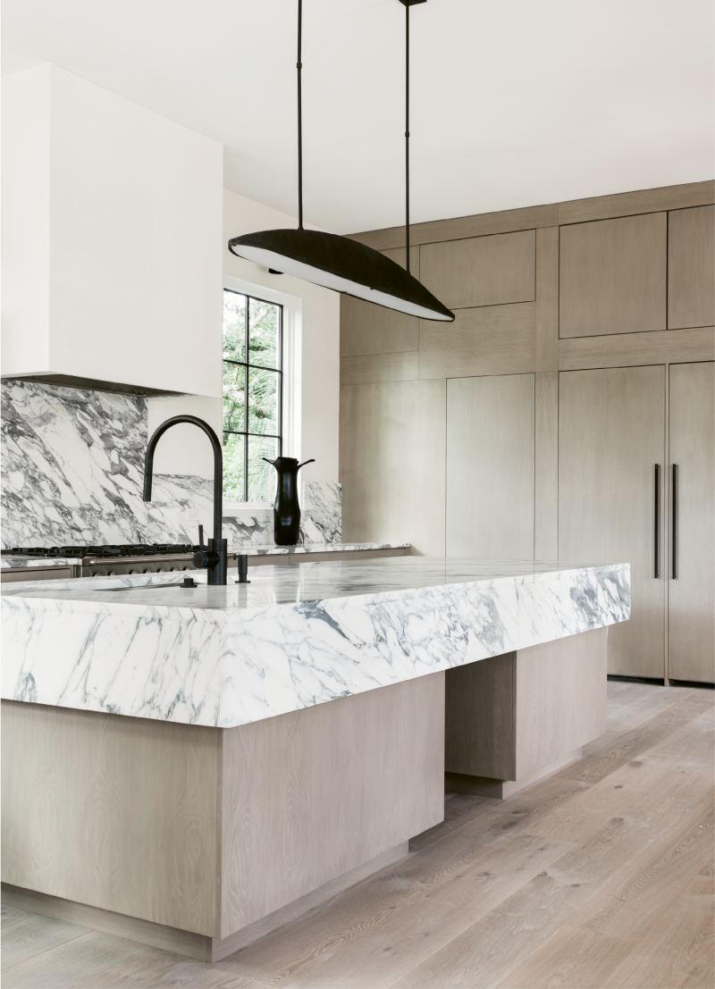 In the light and airy kitchen, white marble countertops with bold black veining make a strong visual impact.
