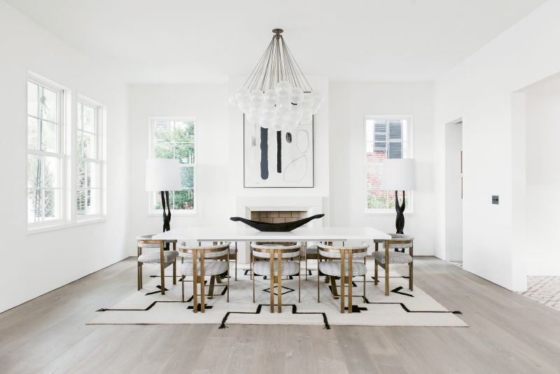 """In the dining room, sculptural elements such as the Apparatus """"Cloud"""" light fixture, Kelly Wearstler dining chairs, and a custom Merida rug woven with leather straps are like functional works of art."""
